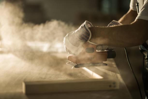 nahaufnahme des männlichen bauarbeiter arbeiten mit sander auf ein holzbrett. - schmirgelmaschine stock-fotos und bilder