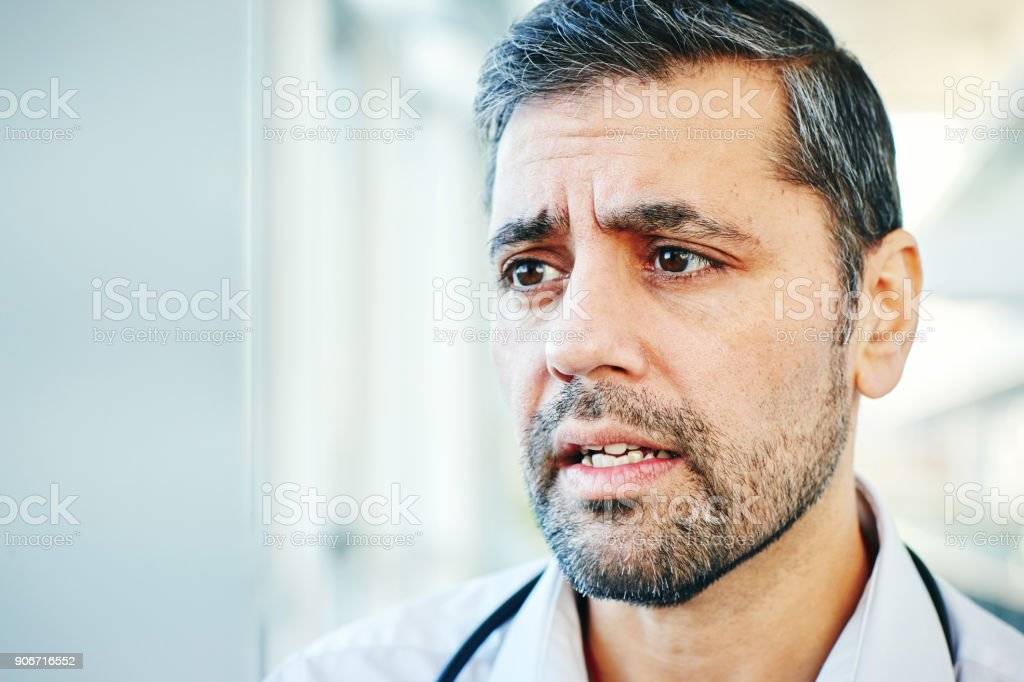 Close up of male doctor face in conversation with staff in hospital