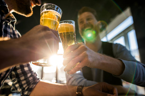 Close up of male friends toasting with beer in a cafe. stock photo