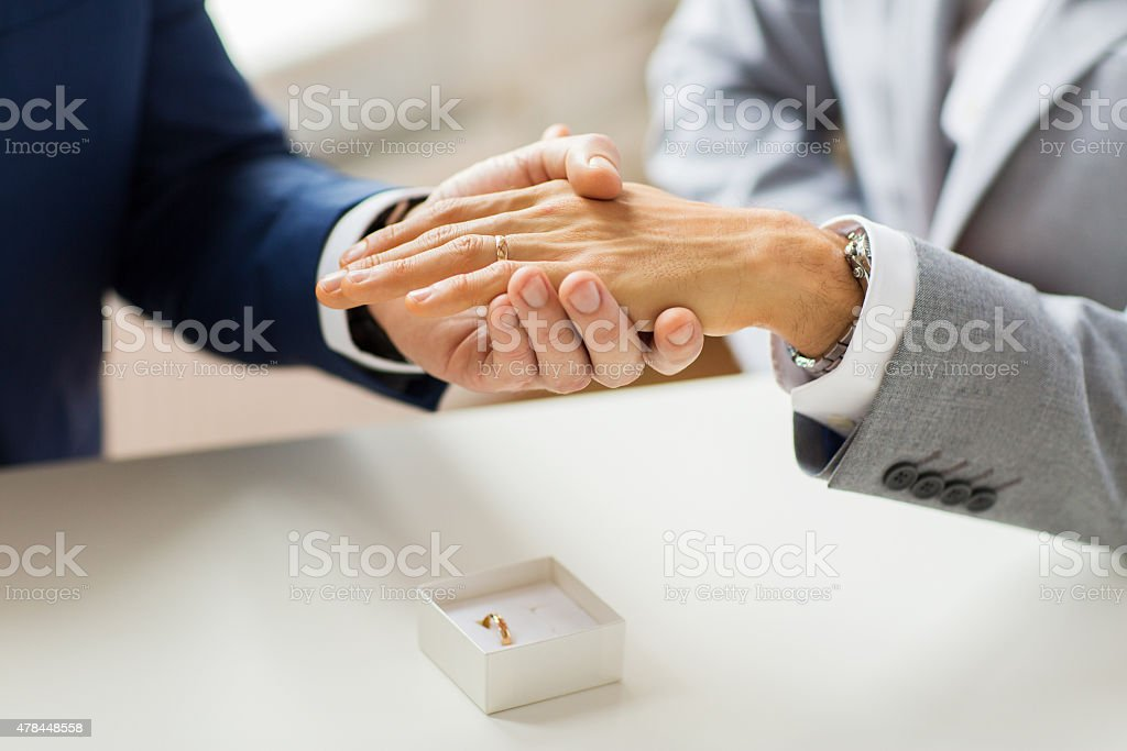 Close Up Of Male Gay Couple Hands And Wedding Ring Stock Photo