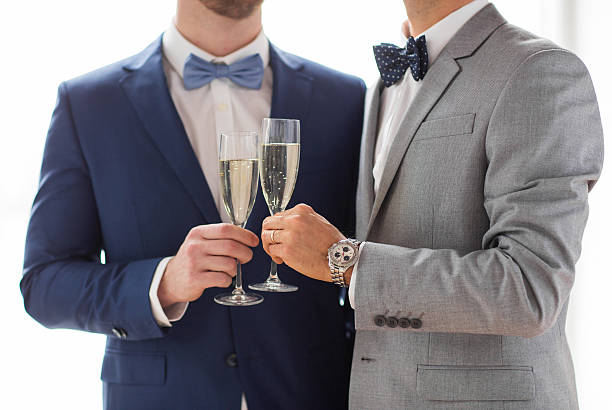close up of male gay couple with champagne glasses stock photo