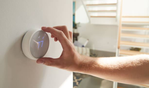 Close Up Of Male Hand Adjusting Digital Central Heating Thermostat In Home stock photo