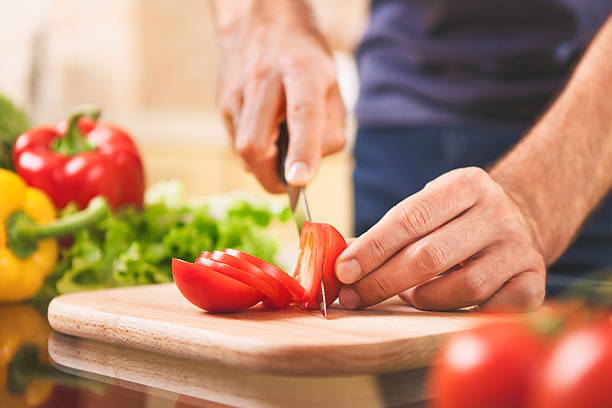 close up of male hand cutting tomato on cutting board – Foto