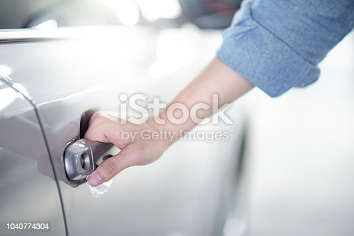 istock Close up of male hand holding and opening the metallic car door handle. Urban lifestyle with automobile concept 1040774304