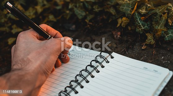 815359666 istock photo Close up of male hand writing in a notepad horizontal outdoor shot 1148166813