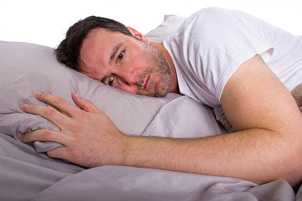 Close Up of Male Insomniac Unable to Sleep in Bed stock photo