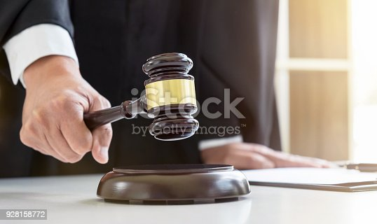 istock Close up of Male lawyer or judge hand's striking the gavel on sounding block, working with Law books, report the case on table in modern office, Law and justice concept 928158772