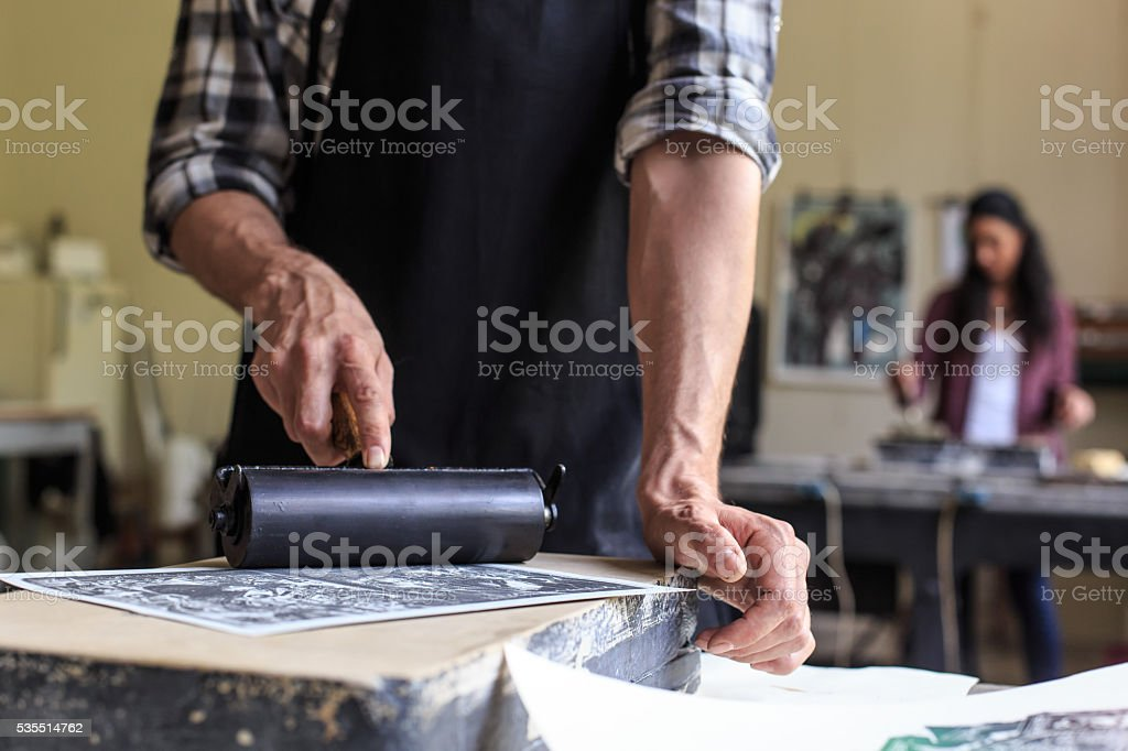 Close up of male lithograph worker using printing roller stock photo