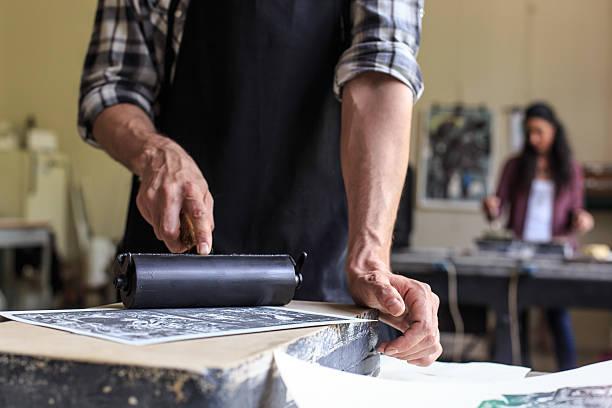 primo piano del maschio litografia operaio con rullo di stampa - acquaforte foto e immagini stock