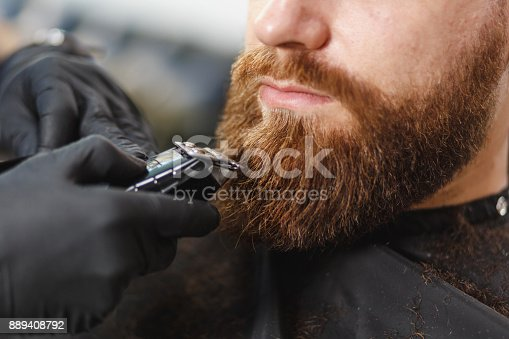 986804130istockphoto Close up of male professional hairdresser serving client with thick big beard by clipper. Ginger handsome brutal stylish young man getting trendy haircut in black cape. Light white barber shop room 889408792