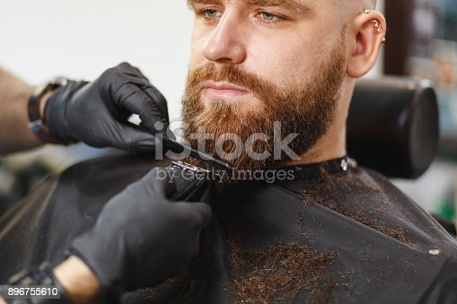 986804130istockphoto Close up of male professional hairdresser serving client with thick big beard by clipper. Ginger handsome brutal stylish young man getting trendy haircut in black cape. Light white barber shop room 896755610