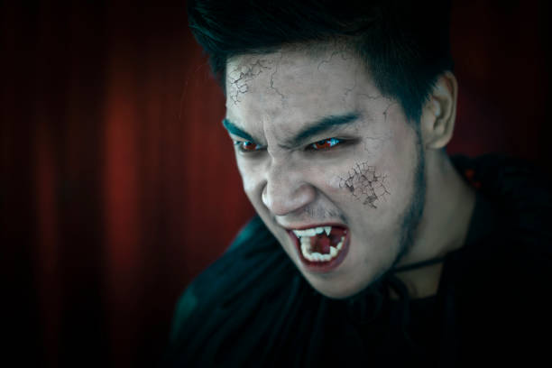 Close up of male vampire in black hood with red eyes. Halloween concept. stock photo
