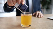 Crop close up of sick male employee pour dissolve powder have hot influenza tea in office, man worker take medication from sachet to relive flu or fever symptoms, high temperature, healthcare concept