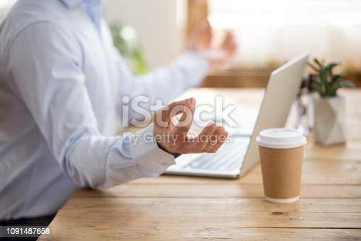 916520034istockphoto Close up of male worker meditate at workplace 1091487658
