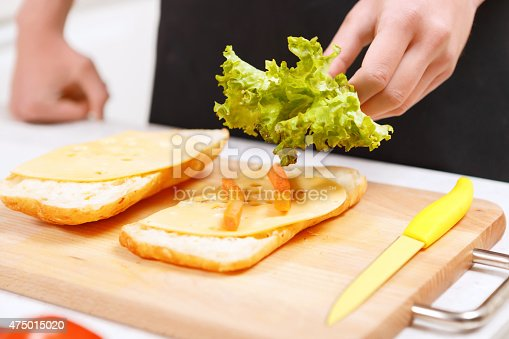 istock Close up of man adding lettuce leaves to sandwich 475015020
