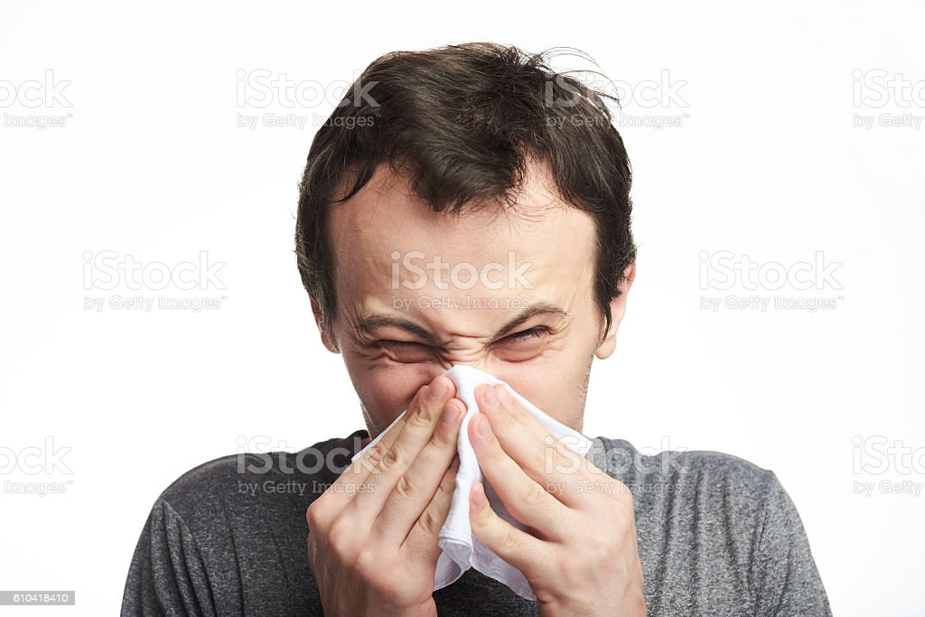 close up of man blowing nose stock photo