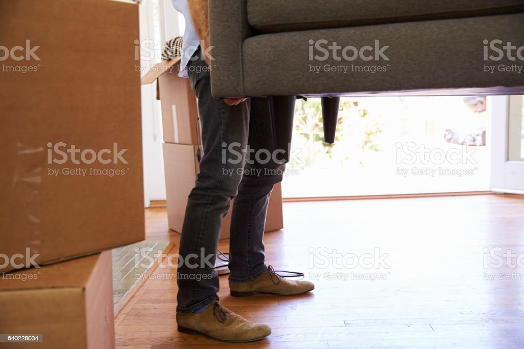 Close Up Of Man Carrying Sofa Into New Home On Moving stock photo