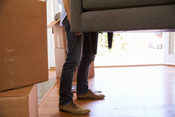 close up of man carrying sofa into new home on moving - physical activity stock photos and pictures