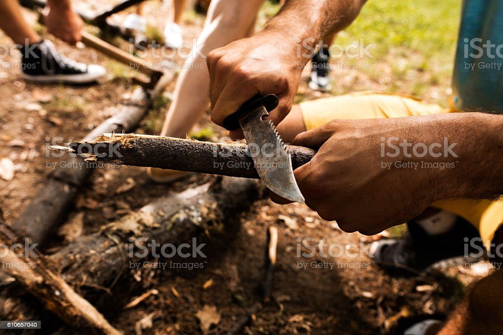 Close up of man carving branch with knife in nature. stock photo