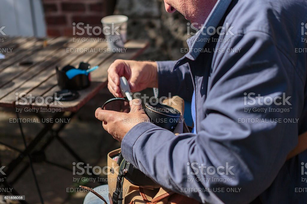 Close up of man cleaning camera equipment stock photo