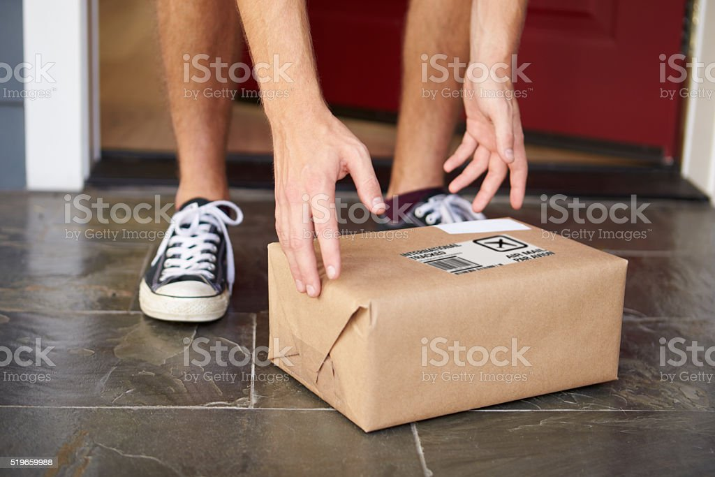 Close Up Of Man Collecting Parcel Delivery Outside Door stock photo & Royalty Free Front Door Package Pictures Images and Stock Photos ...