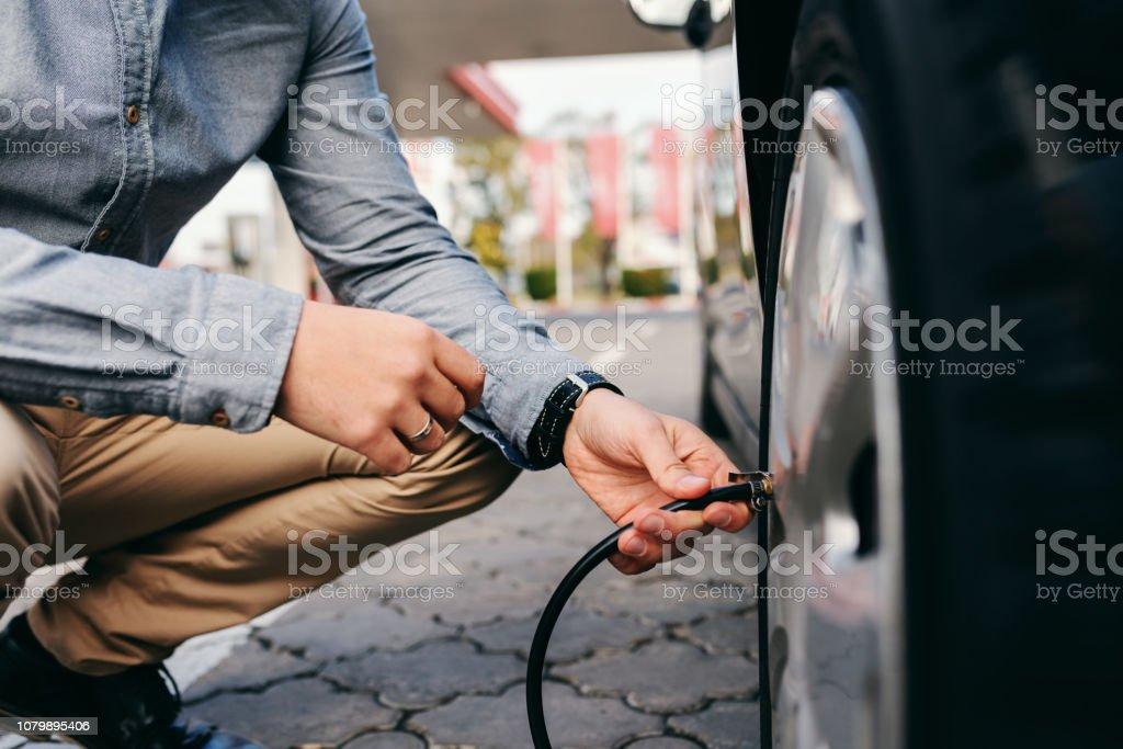 Cerca del hombre agachado en la gasolinera e inflar el neumático. - Foto de stock de Abstracto libre de derechos