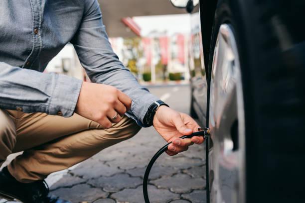 close up van man crouching op het benzinestation en oppompen van de band. - autoband stockfoto's en -beelden