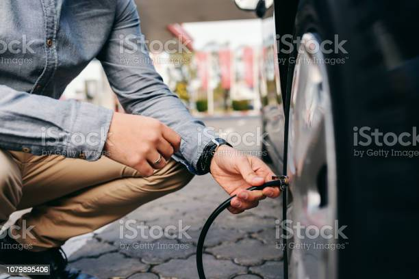 Cerca Del Hombre Agachado En La Gasolinera E Inflar El Neumático Foto de stock y más banco de imágenes de Abstracto
