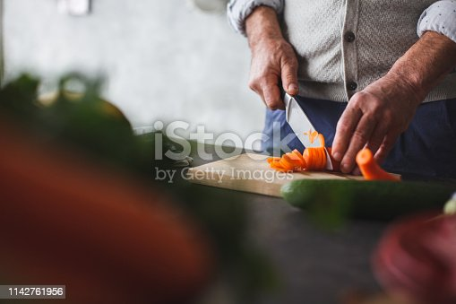 Close up shot of unrecognizable man cutting fresh carrot on the cutting board in the kitchen.