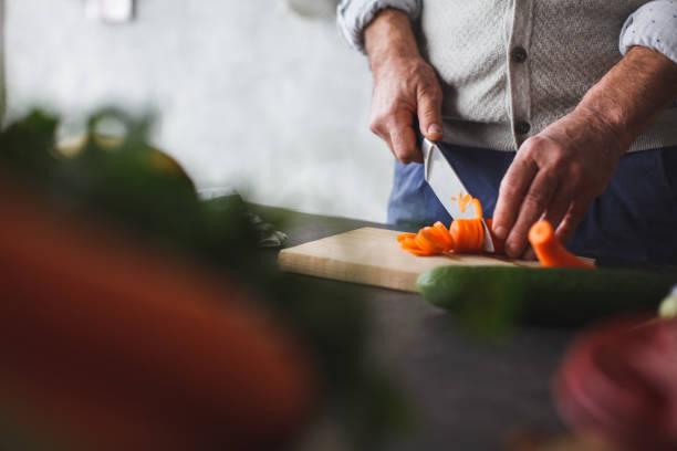 Nahaufnahme des Mannes Schneiden von Karotten – Foto
