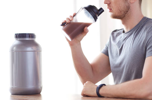 close up of man drinking protein shake stock photo