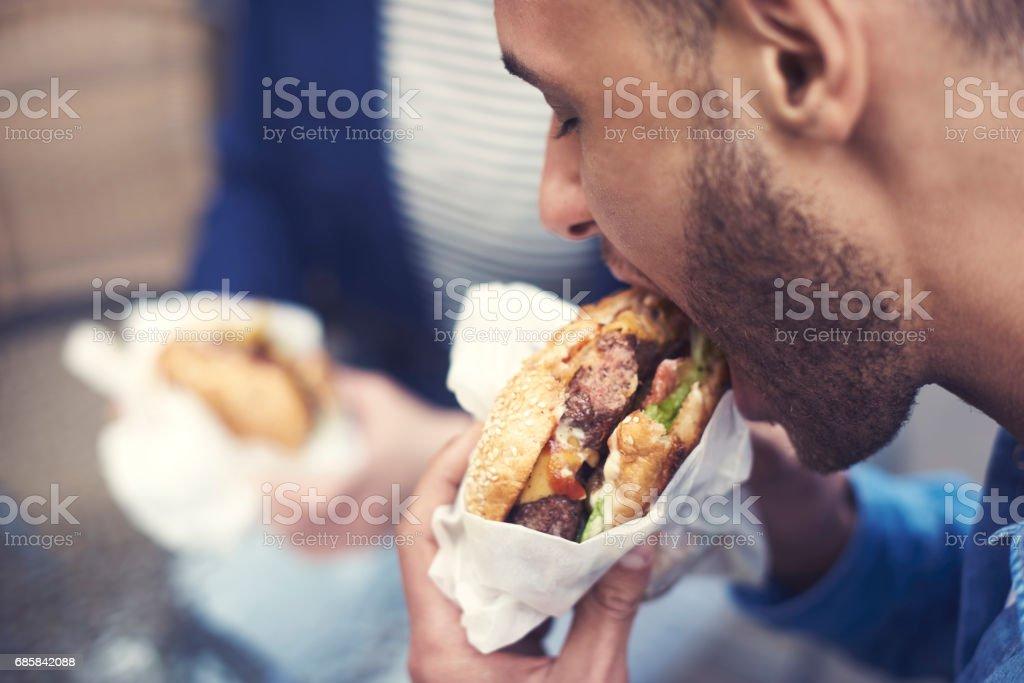 Close up of man eating cheeseburger stock photo