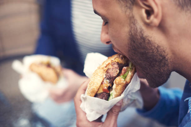 close up of man eating cheeseburger - unhealthy eating stock pictures, royalty-free photos & images