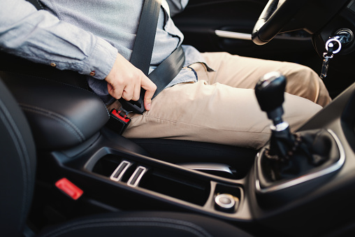 istock Close up of man fastening seat belt while sitting in the car. Safe driving concept. 1079894836