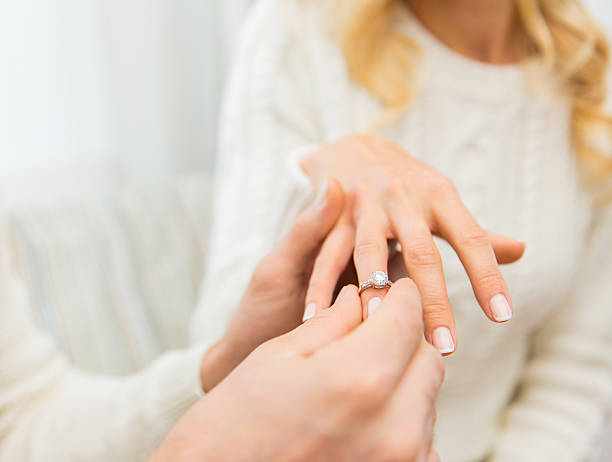 close up of man giving diamond ring to woman - diamond ring hand stock photos and pictures