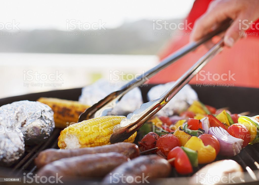 Close up of man grilling food on barbecue stock photo