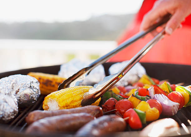 close up of man grilling food on barbecue - barbecue grill stock photos and pictures