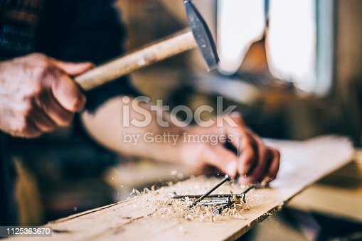 Young handsome carpenter working in his workshop, drinking coffee, talking on the phone, looking work plans DIY