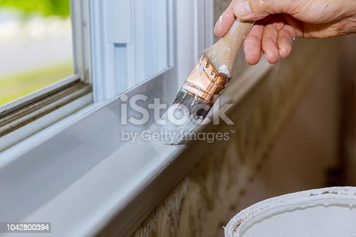 Close up of a man hand carefully painting the edge of an house window