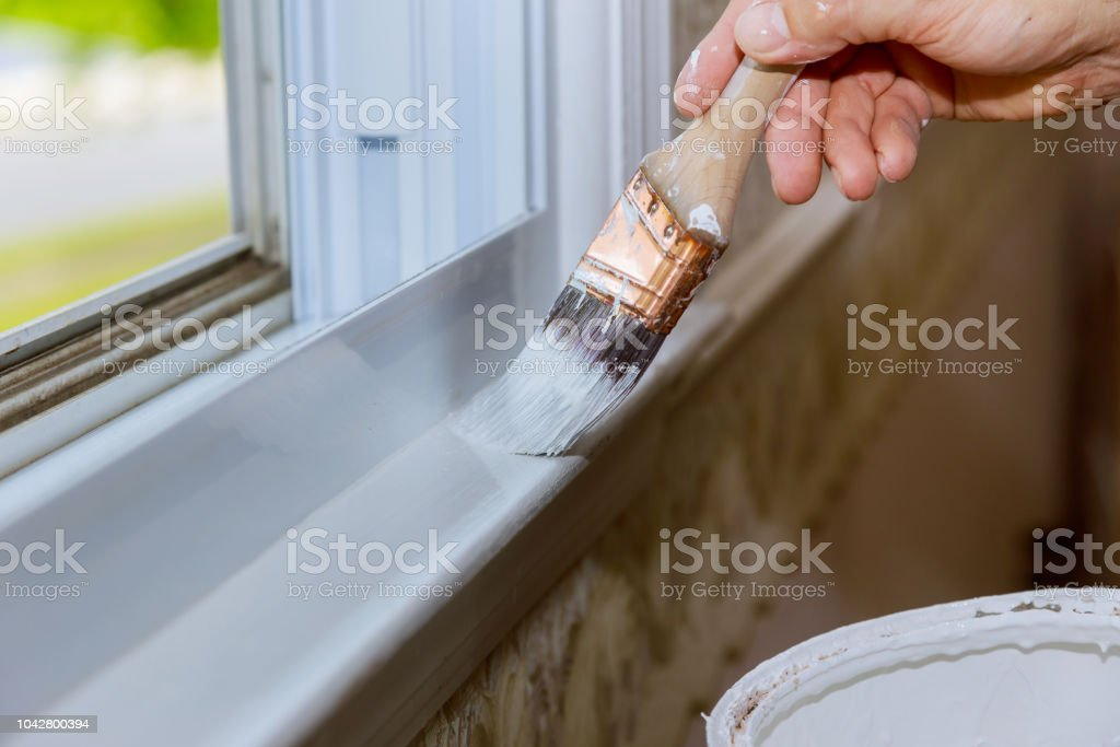 Close up of man hand carefully painting the edge of an house window stock photo