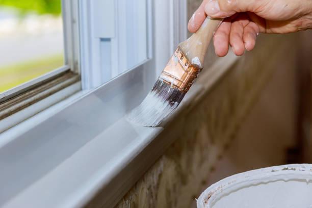 Nahaufnahme eines Mannes Hand vorsichtig den Rand des Fensters ein Haus malen – Foto