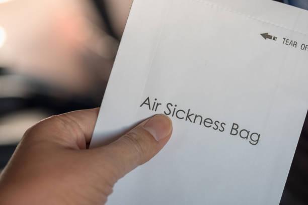 nahaufnahme des mannes hand, die luft krankheit papiertüte auf airplne. - windbeutel stock-fotos und bilder