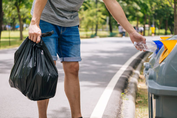 Close up of man hand throwing a plastic bottle into recycle dustbin. Garbage sorting before putting in garbage bin stock photo