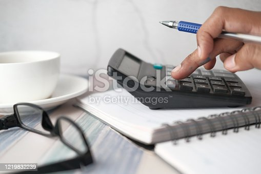 Close up of young man using calculator .