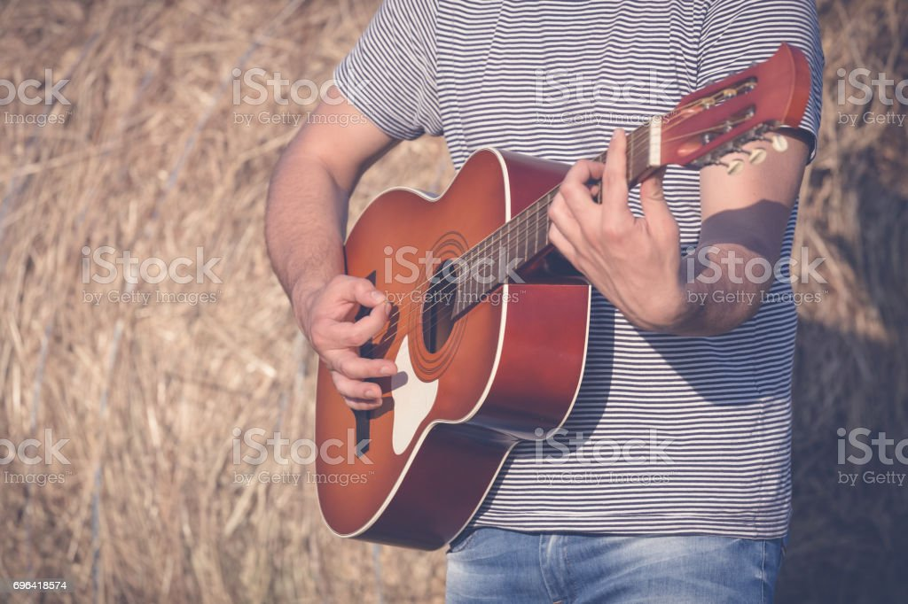 Close up of man hands playing acoustic guitar outdoors. Retro, music and lifestyle concepts. stock photo