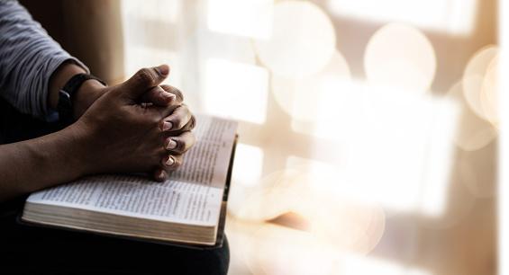 Close up of man hands praying on bible.