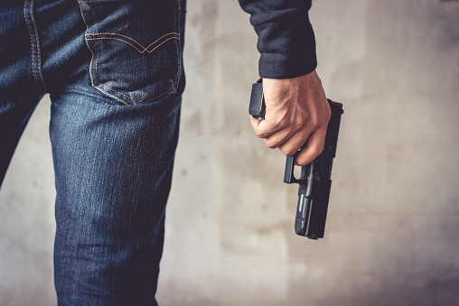 istock Close up of man holding hand gun. Man wearing blue jeans. Terrorist and Robber concept. Police and Soldier concept. Weapon theme 947369238