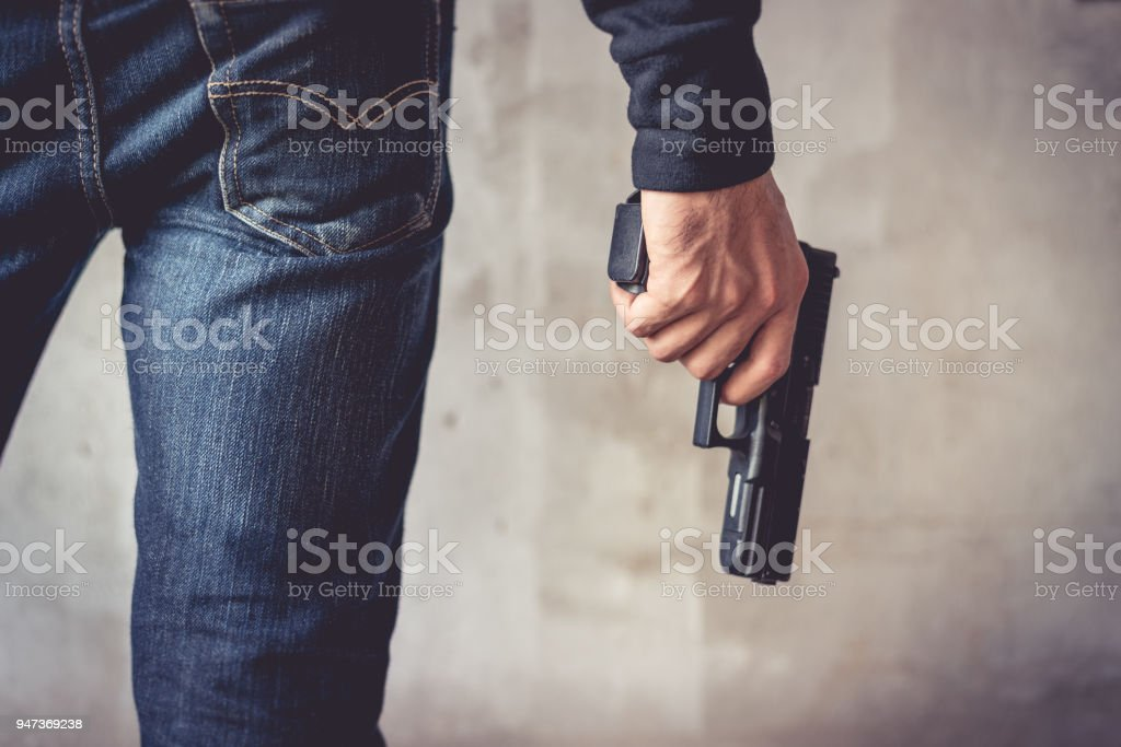 Close up of man holding hand gun. Man wearing blue jeans. Terrorist and Robber concept. Police and Soldier concept. Weapon theme stock photo