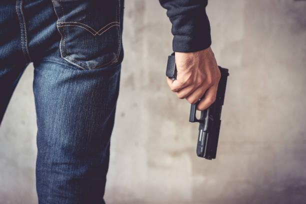 der mann, der handfeuerwaffe hautnah. mann trägt blue jeans. terrorist und räuber konzept. polizei und soldaten-konzept. waffe-thema - schusswaffe stock-fotos und bilder