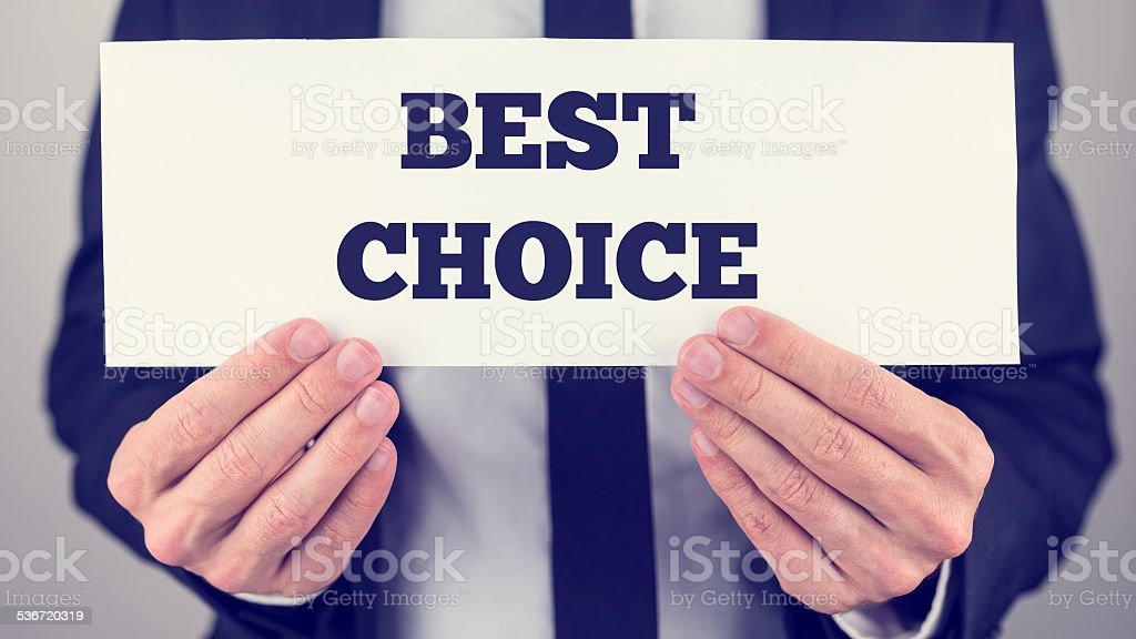 Close Up of Businessman Holding Sign in front of Chest Reading Best...